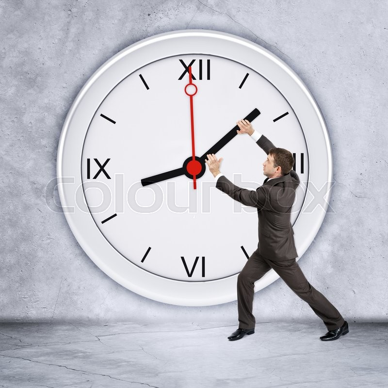 Businessman holding black clock hand on grey wall backgound, stock photo