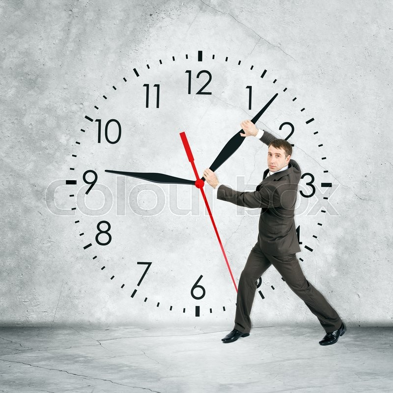 Businessman holding clock hand and looking at camera on grey wall backgound, rear view, stock photo