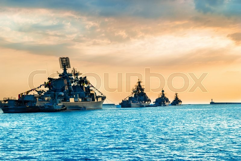 Military navy ships in a sea bay at sunset time, stock photo