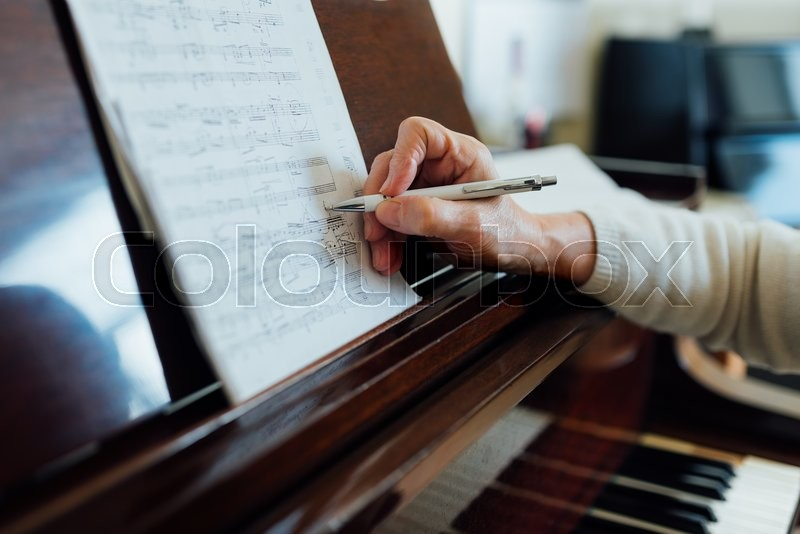 Writing notes on sheet music close-up, stock photo