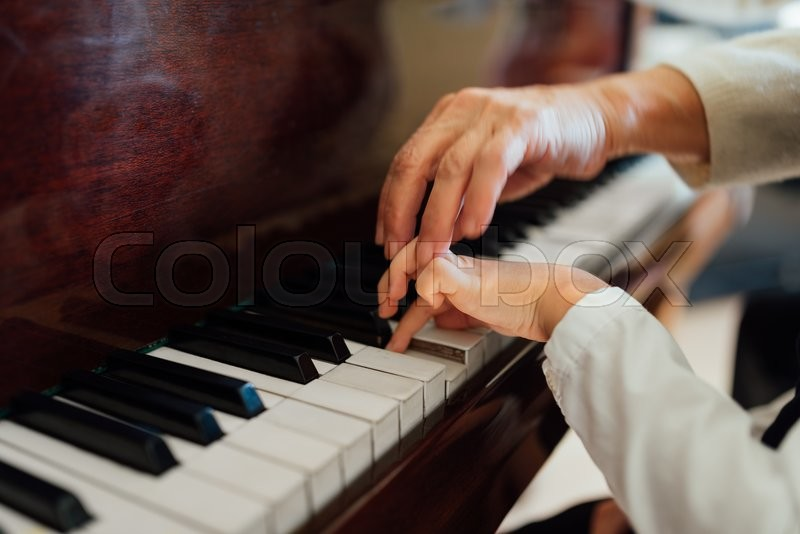 Hand of an experienced pianist, music teacher helping young students, stock photo