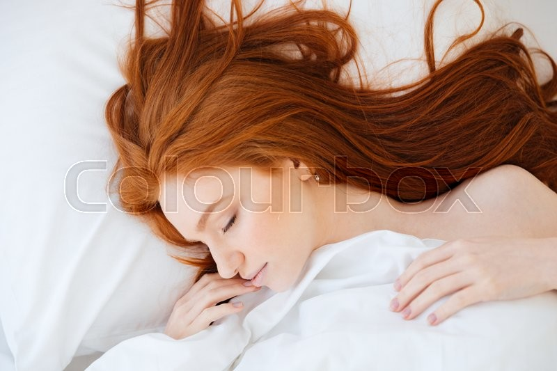 Tender cute young woman with long red hair lying and sleeping in white bed, stock photo