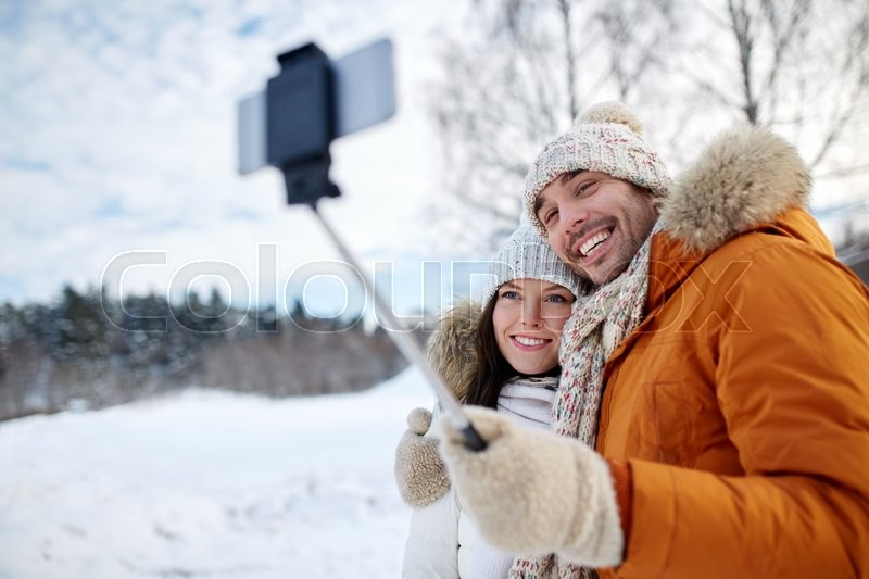 People, season, love, technology and leisure concept - happy couple taking picture with smartphone selfie stick on over winter background, stock photo