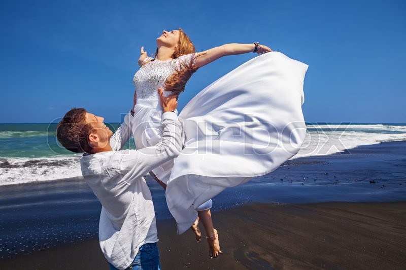 Happy newlywed family has fun on honeymoon holidays on sea black sand beach - married loving man tossing up high in air girl in white flying dress. People activity on summer vacation on island Bali, stock photo