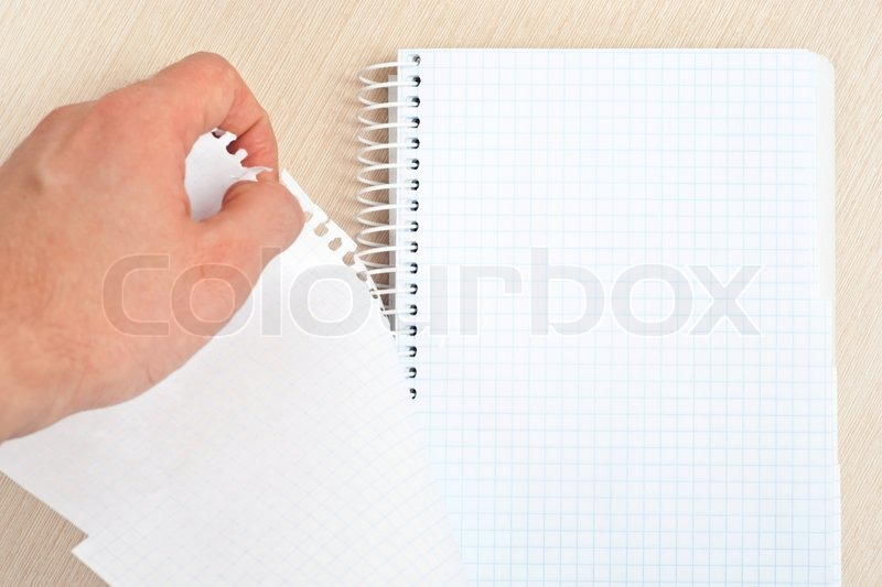 Hand tearing one paper page from notepad on desk, stock photo