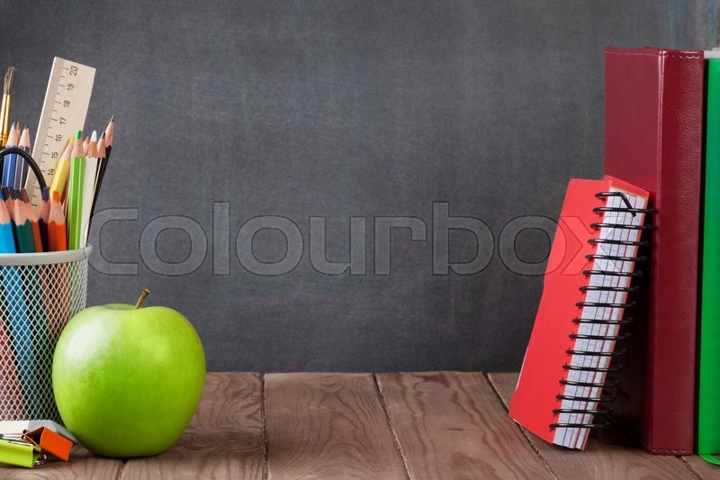 School and office supplies and apple on classroom table in front of blackboard. View with copy space, stock photo