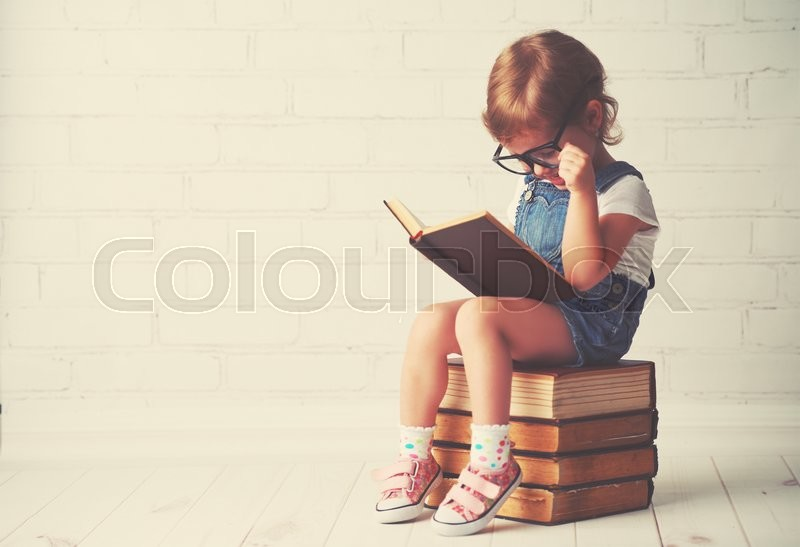 Happy child little girl with glasses reading a books, stock photo