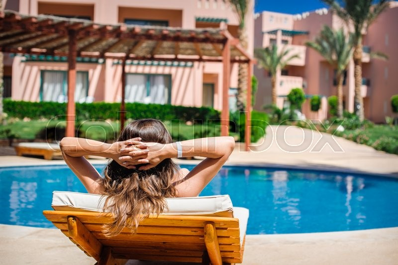 Woman lying on a lounger by the pool at the hotel, stock photo