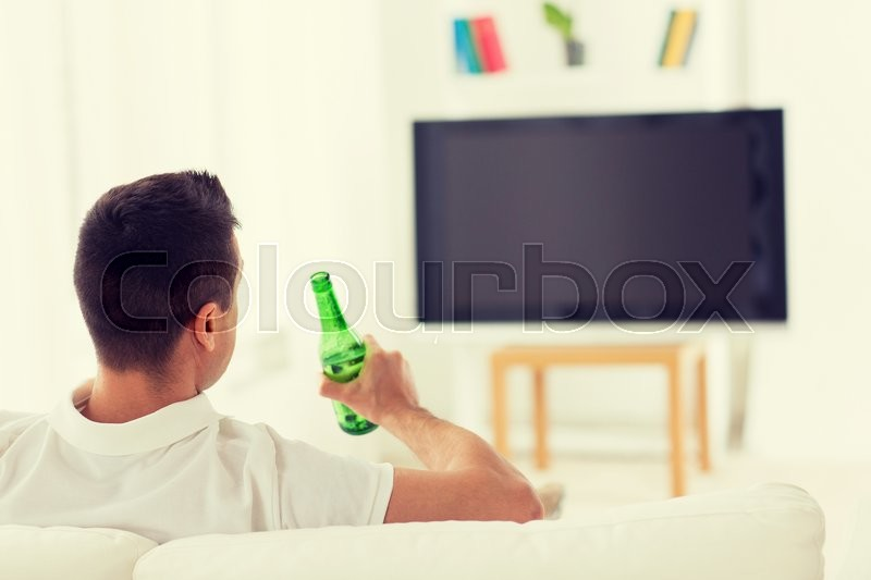 Leisure, technology, mass media and people concept - man watching tv and drinking bottle beer at home from back, stock photo