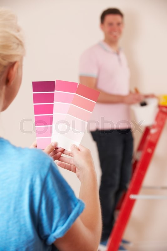 Young Couple Looking At Paint Swatches In New Home, stock photo