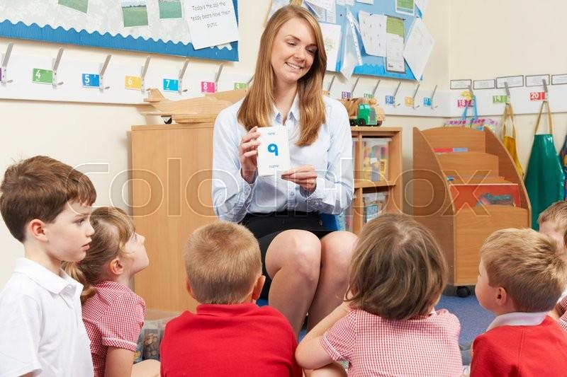 Teacher Using Flash Cards To Teach Maths To Elementary Class, stock photo