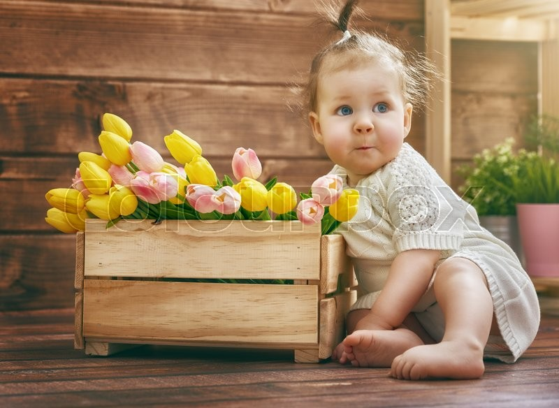 Cute child baby girl with a bouquet of tulips. Mothers day, spring concept, stock photo
