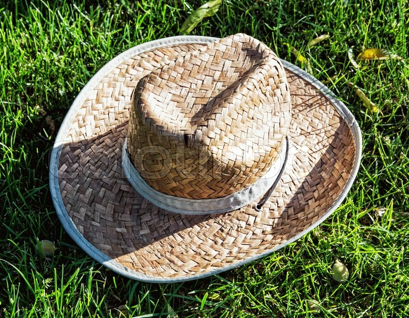 Farmers Yellow Straw Hat In The Grass Rural Symbol Stock Photo
