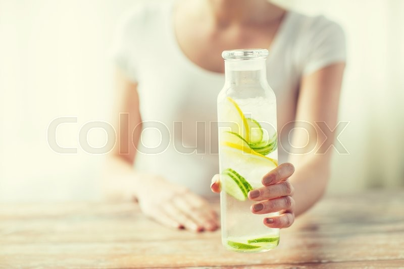 Healthy eating, drinks, diet, detox and people concept - close up of woman with fruit water in glass bottle, stock photo