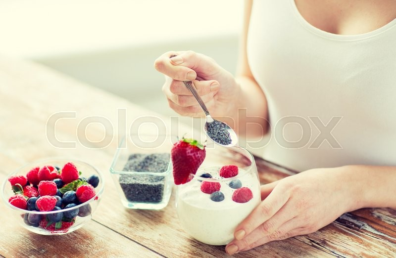 Healthy eating, vegetarian food, diet and people concept - close up of woman hands with yogurt, berries and poppy or chia seeds on spoon, stock photo