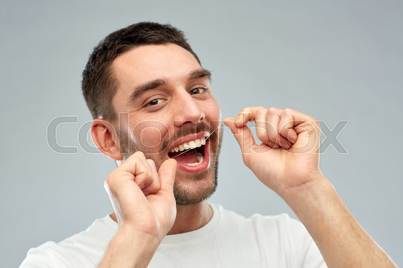 Health care, dental hygiene, people and beauty concept - smiling young man with floss cleaning teeth over gray background, stock photo