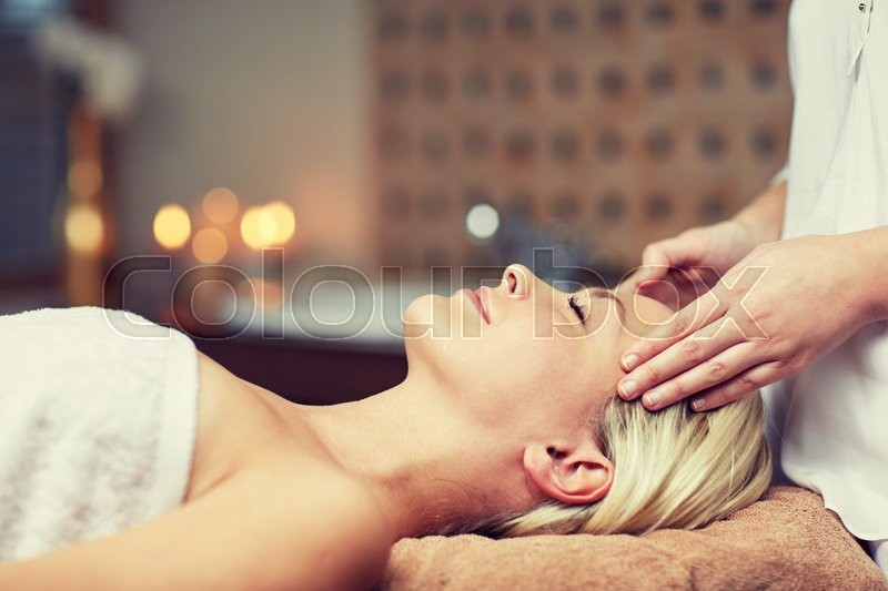 People, beauty, spa, healthy lifestyle and relaxation concept - close up of beautiful young woman lying with closed eyes and having face or head massage in spa, stock photo