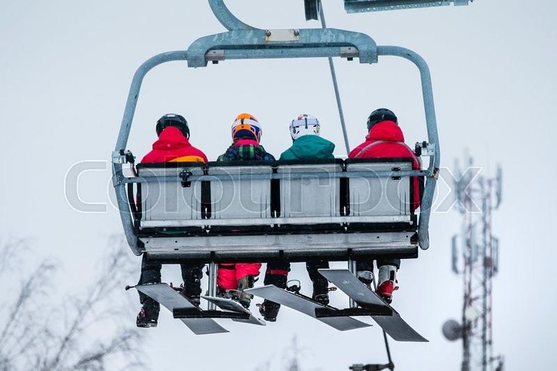 Group young girls snowboard rises to top of mountain on ski lift, stock photo