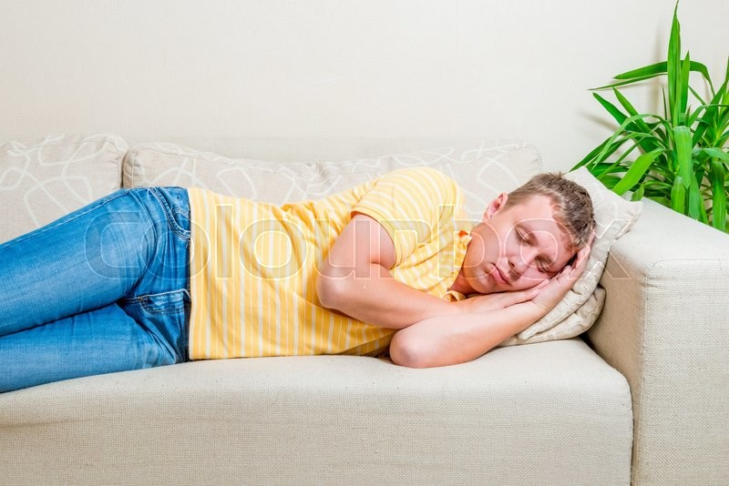 Tired man lay down to take a nap on the sofa in the living room, stock photo