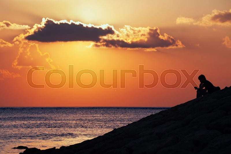 Black silhouette of thinking man sitting alone on the sea beach reading message on mobile phone on sunset sky background. Lifestyle, single people emotions, family conflicts and problem concepts, stock photo
