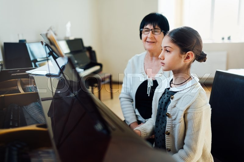 Piano lessons at a music school, teacher and student, stock photo