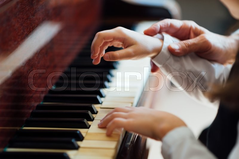 Experienced master piano hand helps the student, close-up, stock photo