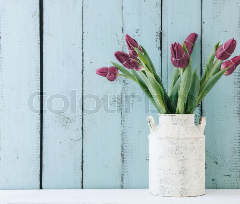 Bouquet of tulip flowers in vintage vase on the shelf over blue wooden background, shabby chic interior decor, stock photo