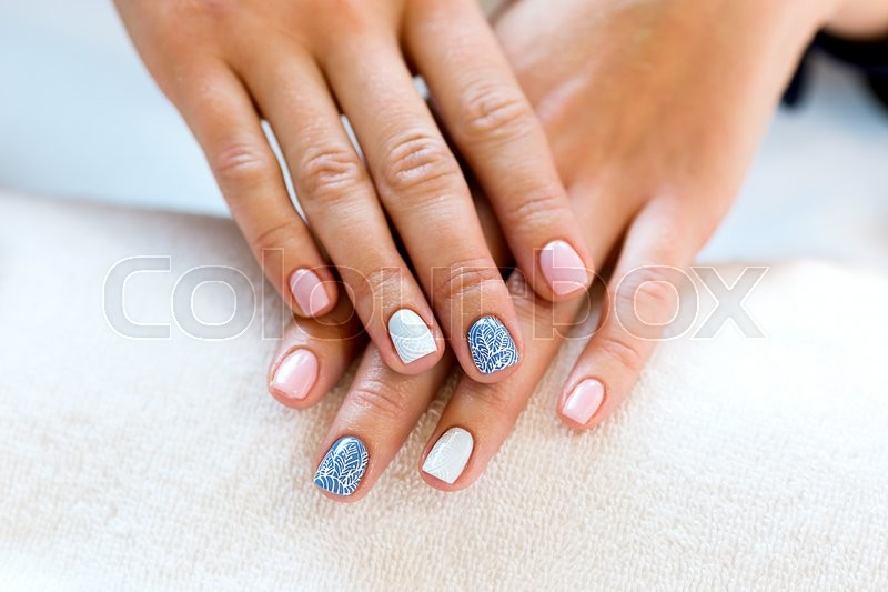 Female hands manicure close up view. Delicate spring manicure. Nail painting. Drawing on nails. Beautiful well-groomed hands with manicure and varnish on nails and artistic painting, stock photo