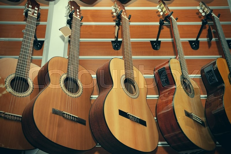 Row of classical acoustic guitars in musical store, stock photo