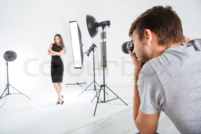 Photographer working with model in studio with softboxes, stock photo
