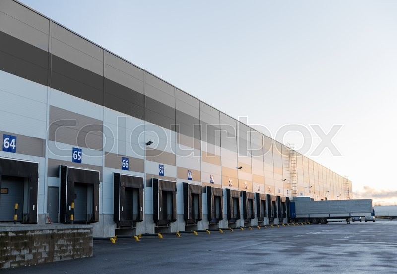 Logistic, storage, shipment, transportation and loading concept - warehouse gates and truck loading, stock photo