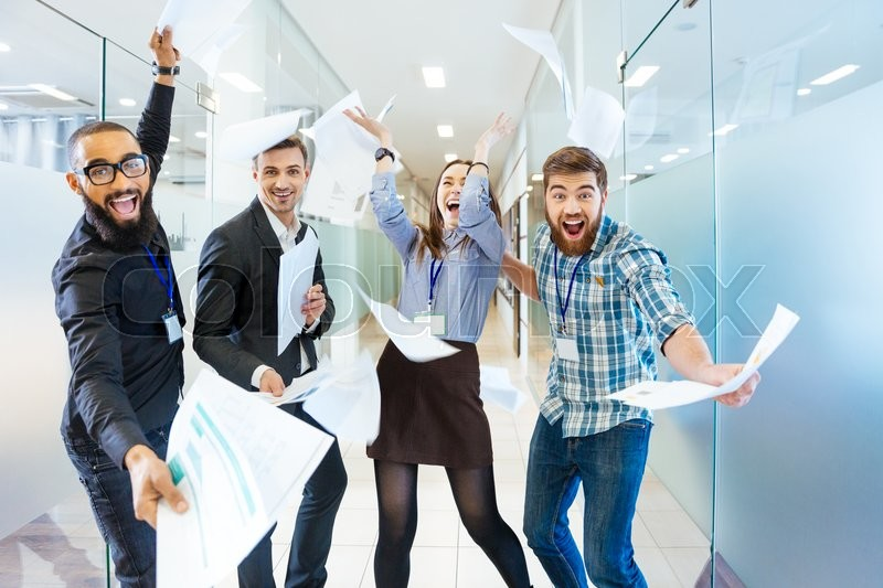 Group of joyful excited business people throwing papers and having fun in office, stock photo