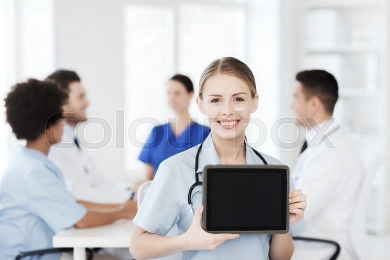 Clinic, profession, people and medicine concept - happy female doctor showing tablet pc computer blank screen over group of medics meeting at hospital, stock photo