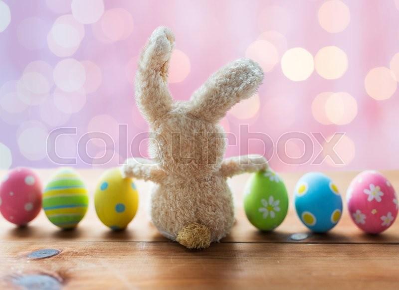 Easter, holidays, tradition and object concept - close up of colored easter eggs and bunny over pink holidays lights background, stock photo
