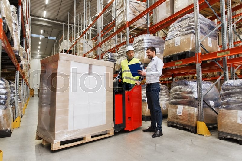 Wholesale, logistic, people and export concept - manual worker on forklift loader and businessmen with clipboard at warehouse, stock photo