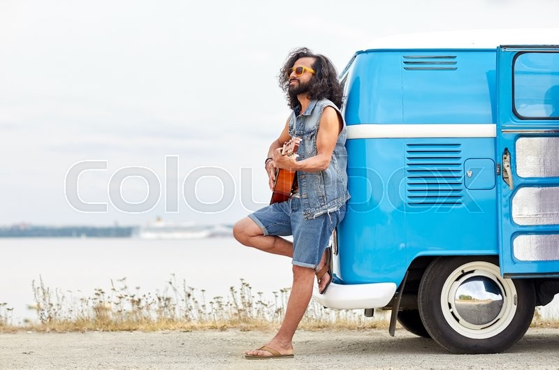 Nature, summer, youth culture, music and people concept - young hippie man playing guitar and singing over minivan car on beach, stock photo