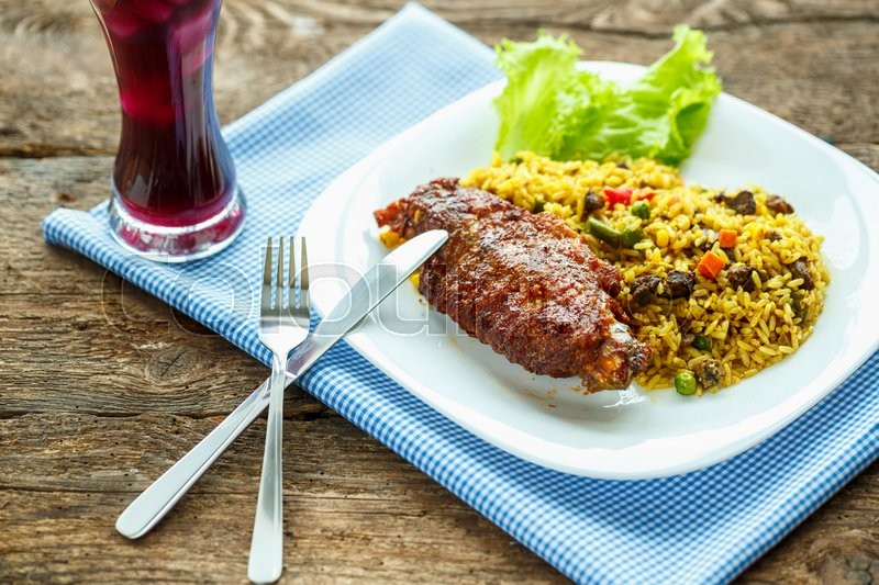 Delicious dishes from turkey meat with rice and salad leaves and a glass of juice with ice, stock photo