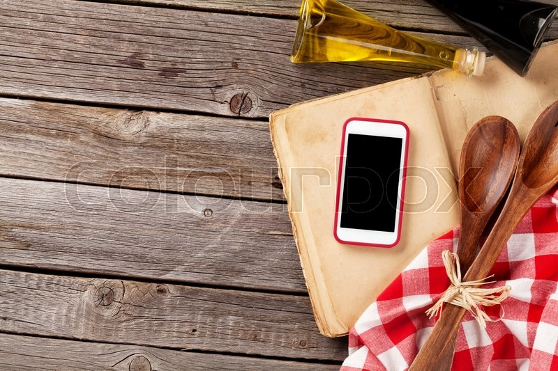 Kitchen table with ingredients, utensils and smartphone with blank screen for your app over cooking book on wooden table. Top view with copy space, stock photo