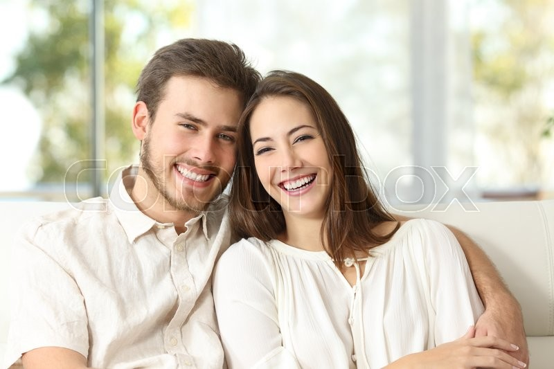 Happy couple sitting on a couch at home and looking at camera, stock photo