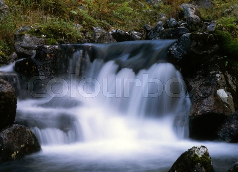 Flowing water of mountain waterfall, stock photo