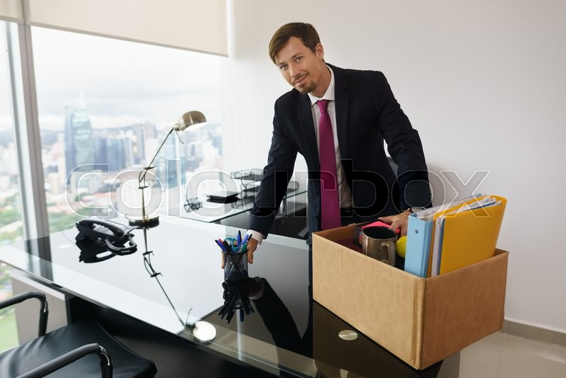 Beau Businessman Recently Hired For Corporate Job Moves Into His New Executive  Office With A View Of The City. He Takes Office Supplies Out Of A Box And  Smiles ...