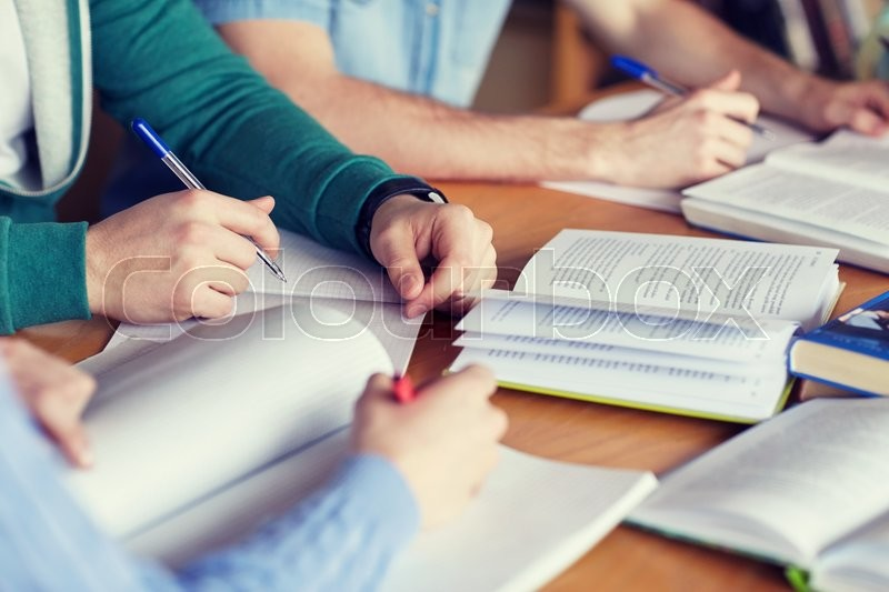 People, learning, education and school concept - close up of students hands with books or textbooks writing to notebooks, stock photo