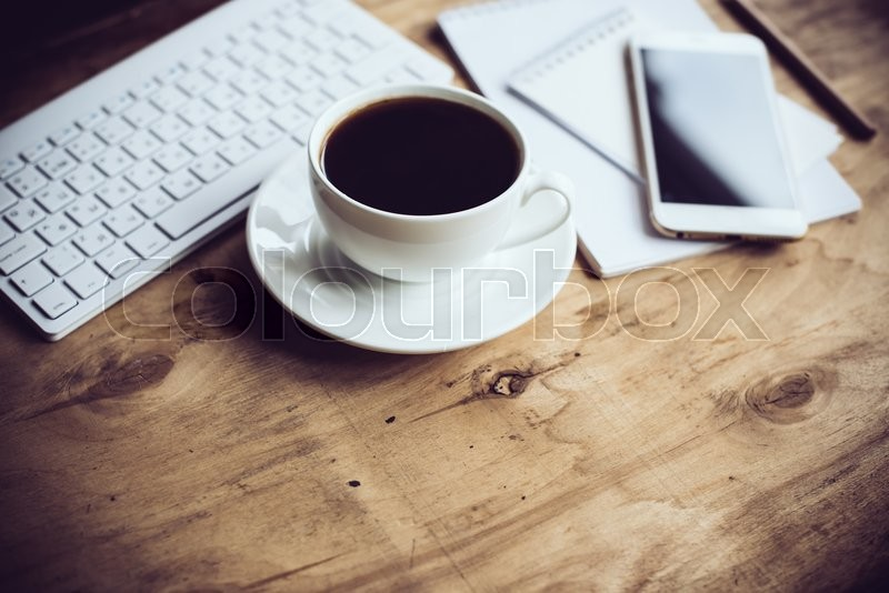Vintage hipster style office table decor with cup of coffee, computer keyboard and smart phone. Blogger\'s modern workspace, interior details with copy space, stock photo