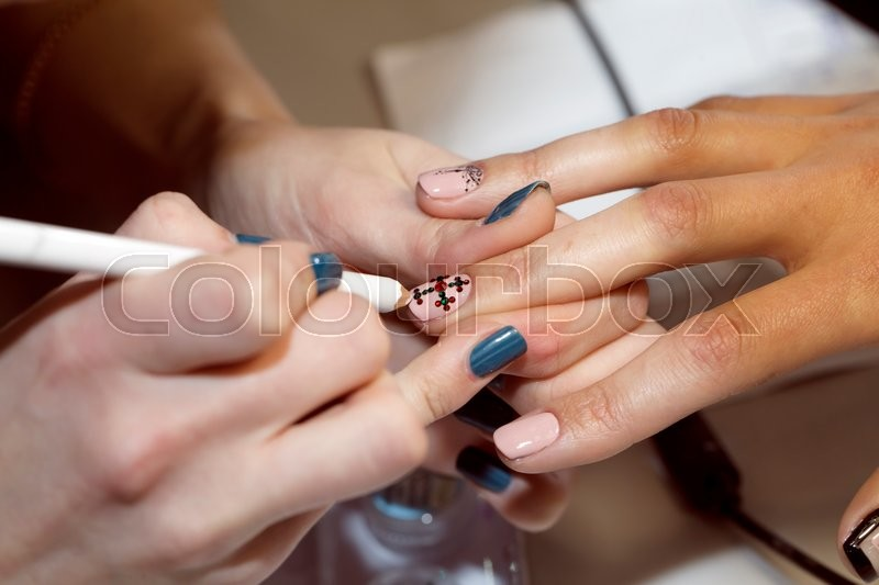 Manicurist makes the new gel polish manicure, close-up, beauty and body care, stock photo