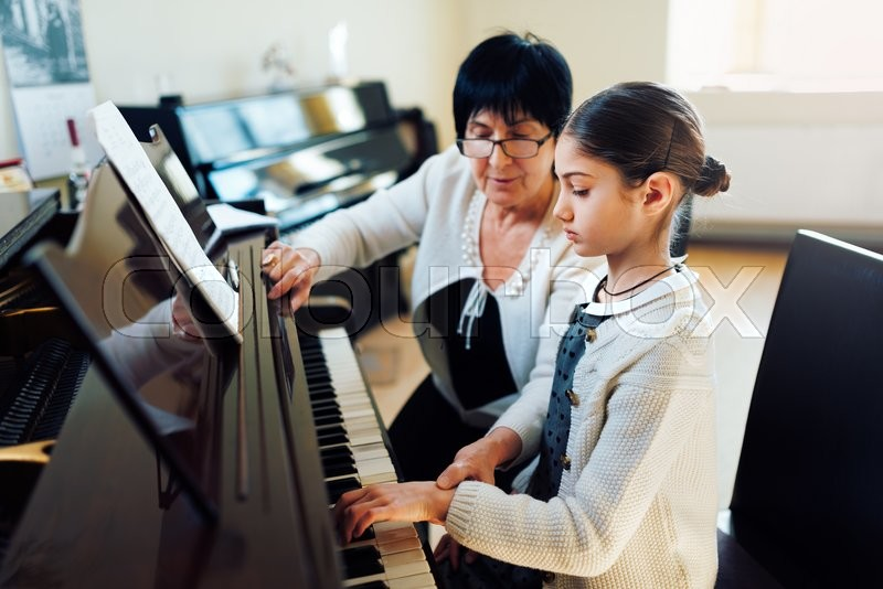A music teacher with the pupil at the lesson piano, stock photo