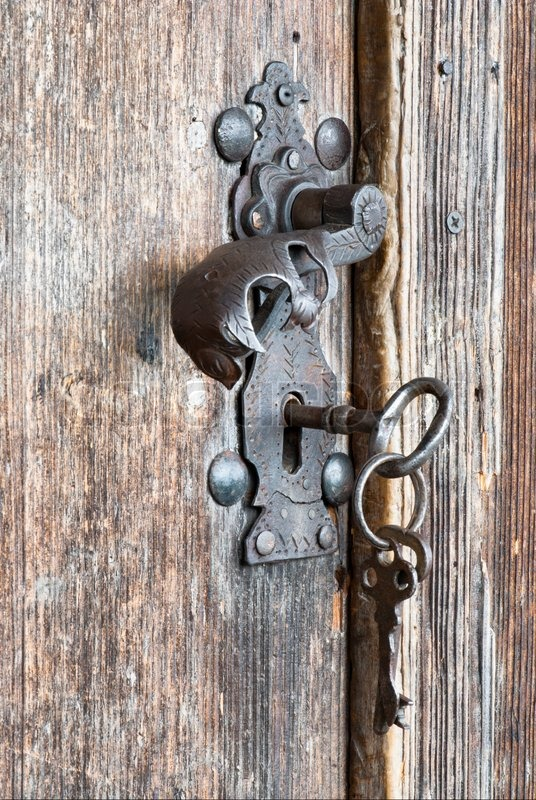 An Old Metal Handle And Keys At Wooden Door Stock Photo
