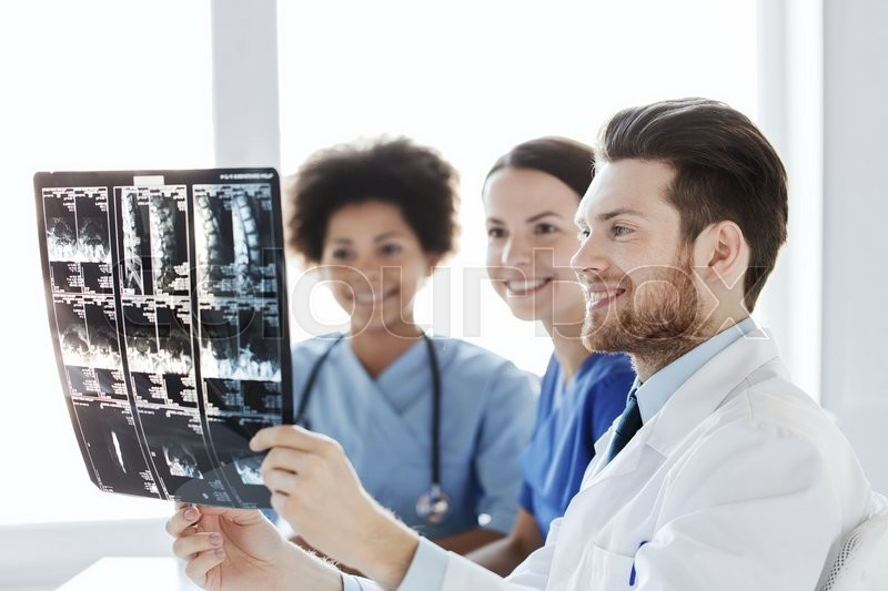 Radiology, surgery, health care, people and medicine concept - group of happy doctors looking to and discussing x-ray image of spine at hospital, stock photo