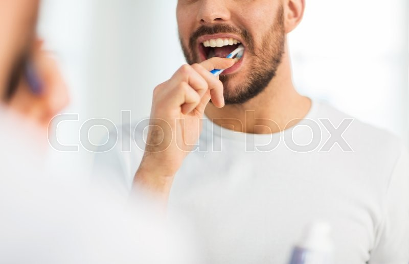 Health care, dental hygiene, people and beauty concept - close up of young man with toothbrush cleaning teeth and looking to mirror at home bathroom, stock photo