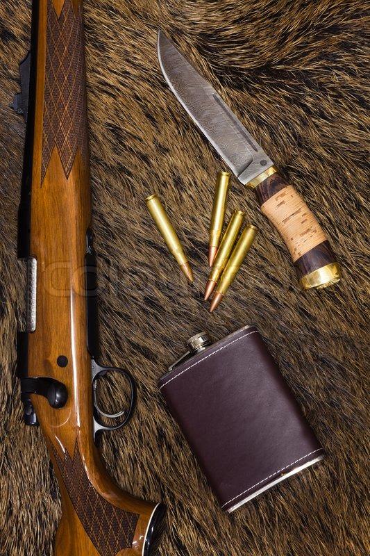 Lovačko oružje i municija 1784052-gewehr-patronen-messer-und-flasche-auf-einem-wildschwein-haut