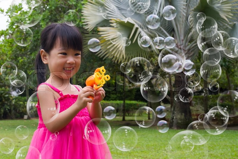 Asian Little Chinese Girls Shooting Bubbles from Bubble Blower in the Park, stock photo